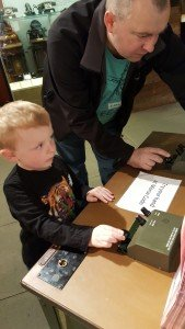 Tapping out morse code. Father and son enjoy a day at The Royal Signals Museum.